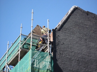 photo of masonry repair on paprapet wall in downtown Toronto Ontario shows scaffolding set up on commercial buidling